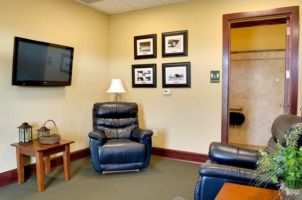 A spacious airport lounge, at the Stanly County Airport. Featuring couches, chairs, book shelfs, a TV, and cozy fireplace.